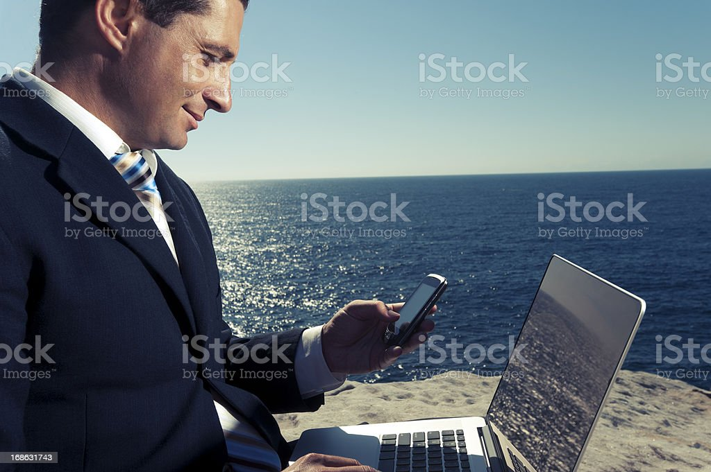 Relaxed businessman working on laptop outdoors. royalty-free stock photo
