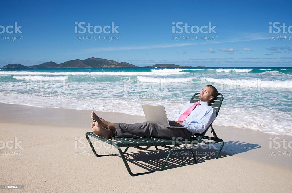 Relaxed Businessman Working with Laptop on Beach Chair royalty-free stock photo