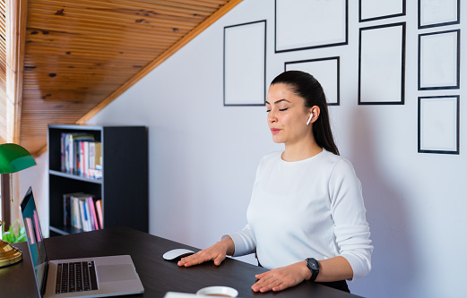 Relaxed calm business woman take deep breath of fresh air resting with eyes closed at work in home office. Doing office yoga and meditating with closed eyes.