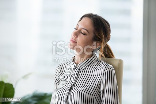 istock Relaxed calm businesswoman resting in ergonomic chair lounging at work 1129638602
