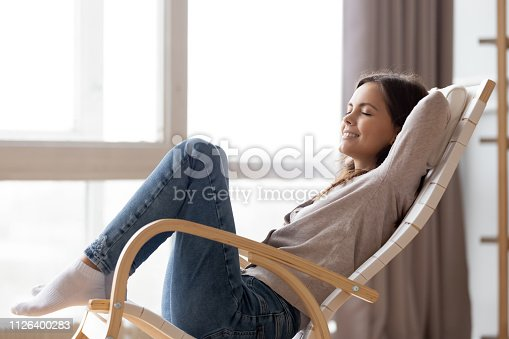 istock Relaxed calm young woman lounging sitting in comfortable rocking chair 1126400283