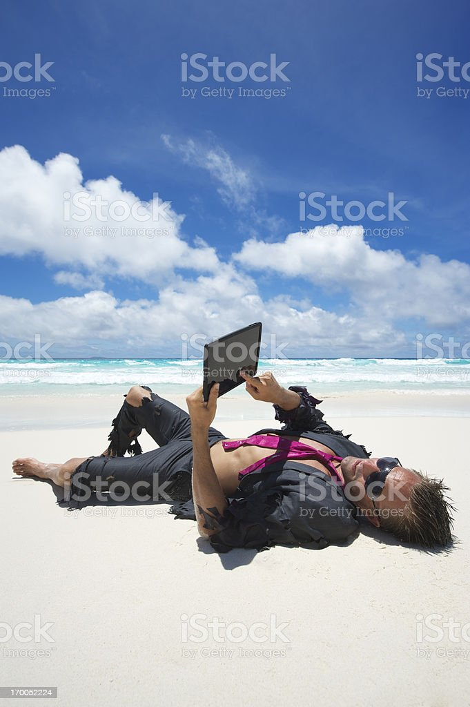 Relaxed Castaway Businessman Using Tablet Computer on Beach royalty-free stock photo