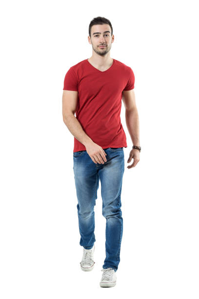relaxed casual man in jeans and red t-shirt walking and looking at camera - près de photos et images de collection