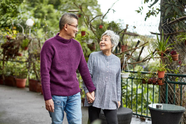 Relaxed Chinese Senior Couple Holding Hands and Walking stock photo