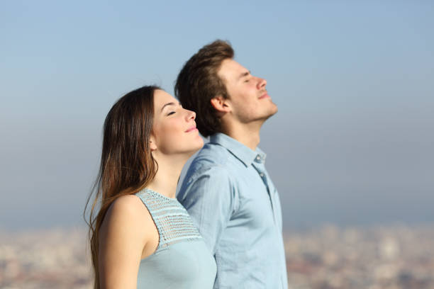 Relaxed couple breathing fresh air with urban background stock photo