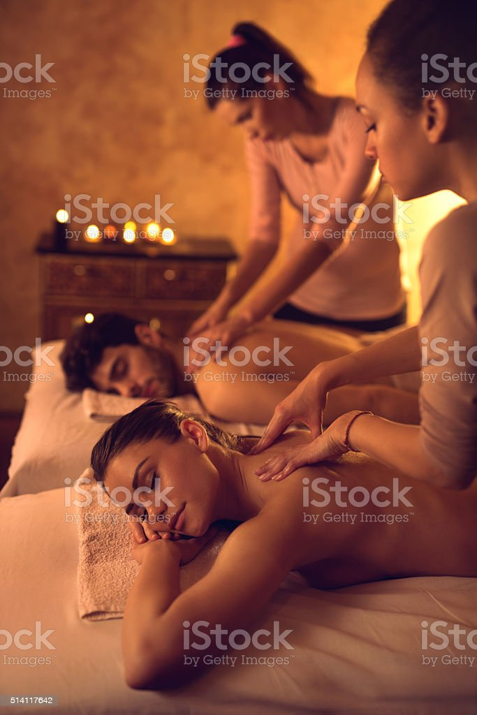 Relaxed couple enjoying during back massage at the spa. stock photo