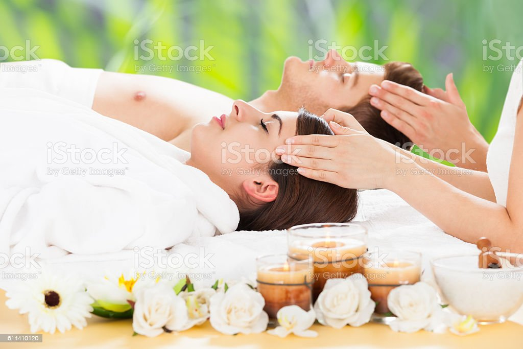Relaxed Couple Receiving Head Massage At Spa stock photo
