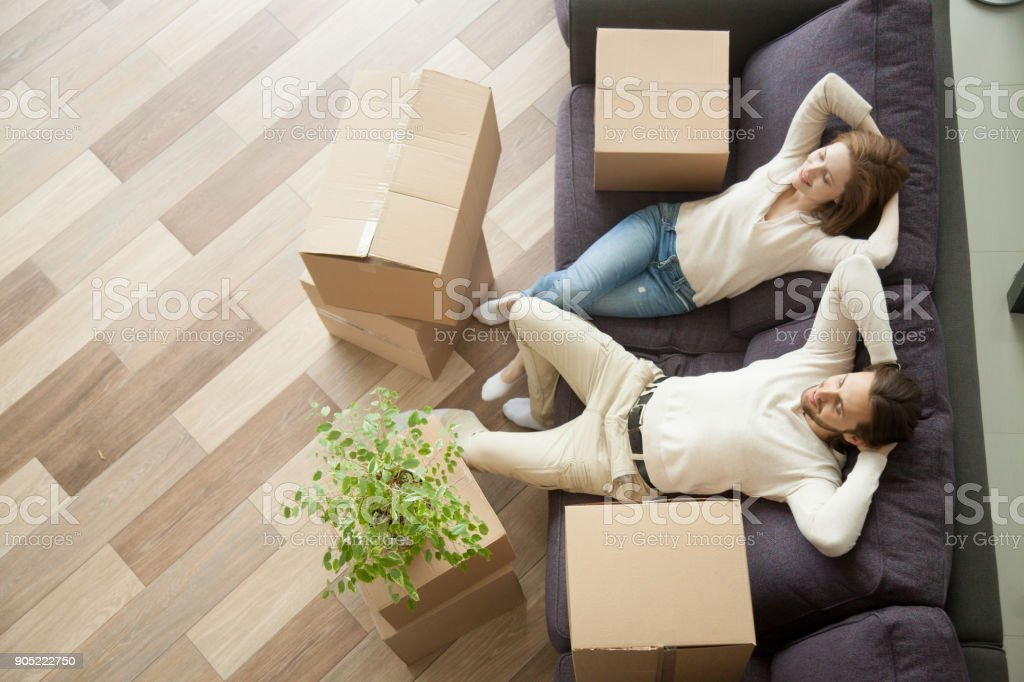 Relaxed couple resting on couch after moving in new home stock photo
