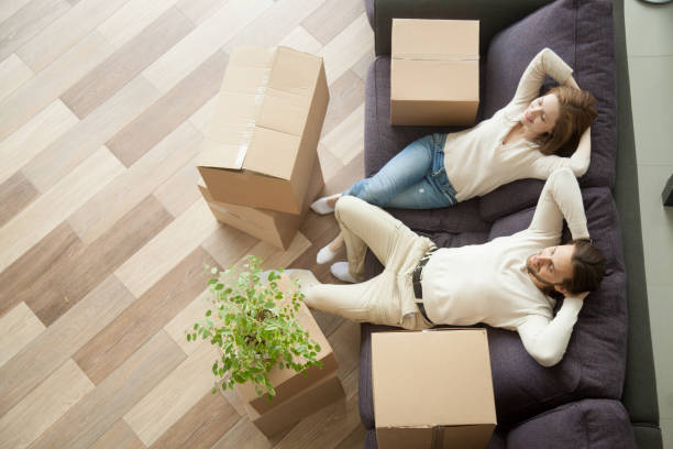 relaxed couple resting on couch after moving in new home - tenant stock photos and pictures