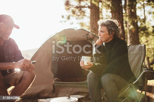 Portrait of relaxed mid adult couple sitting outside tent while camping nearby lakeside on a sunny day. Woman holding coffee talking with man.