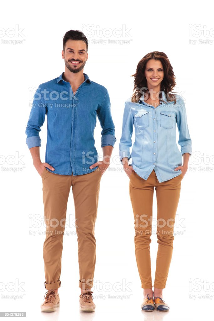 relaxed couple standing with hands in pockets stock photo