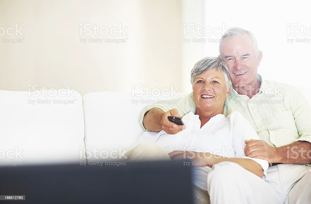 Relaxed couple watching television in living room stock photo