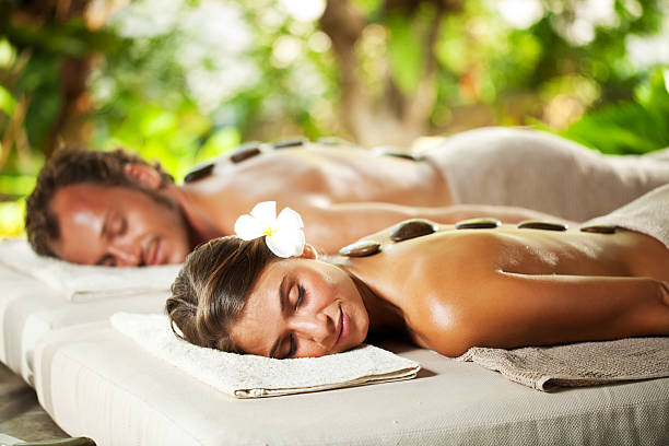 relaxed couple with eyes closed receiving hot stone therapy - thai massage stock photos and pictures