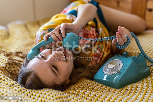 Beautiful young woman of 30 in bed, late in the morning using a vintage phone to talk to a friend