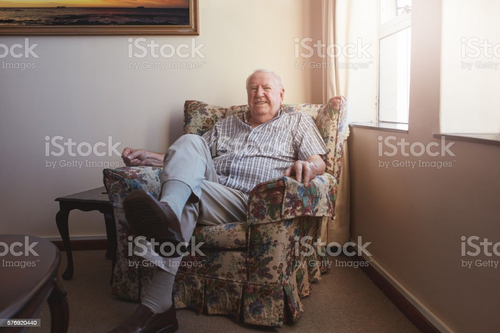 Relaxed elderly man sitting on a arm chair stock photo