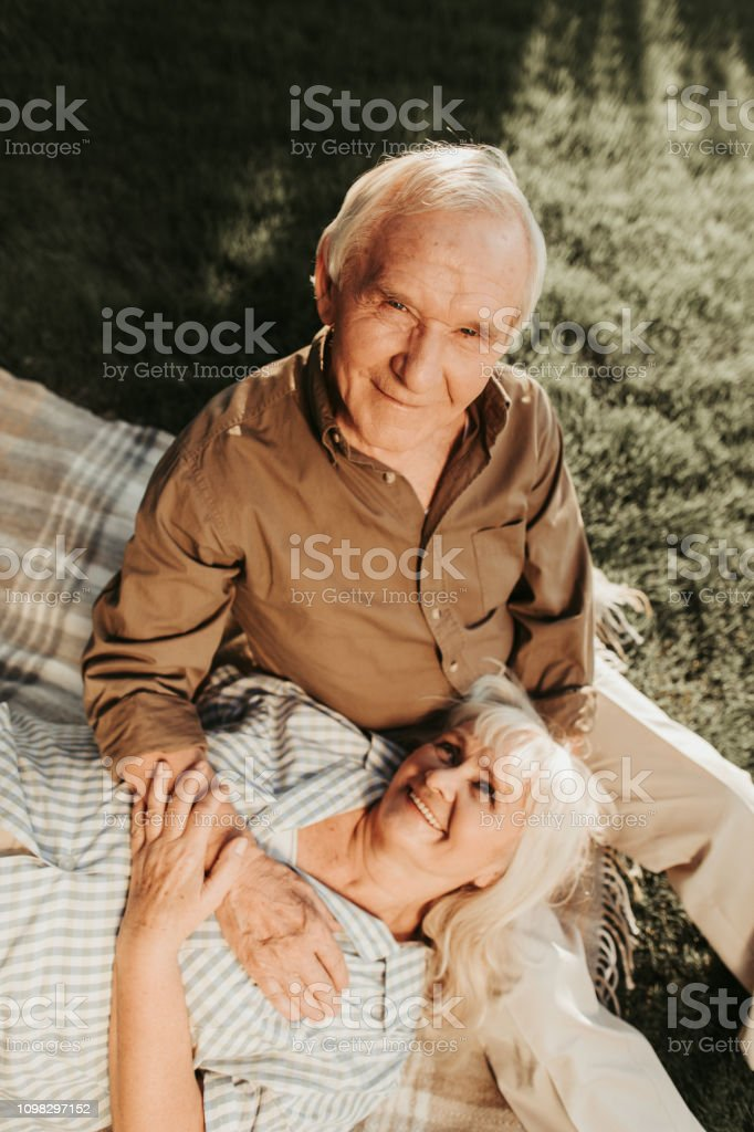 Attentively looking at camera old confident man while her wife lying...