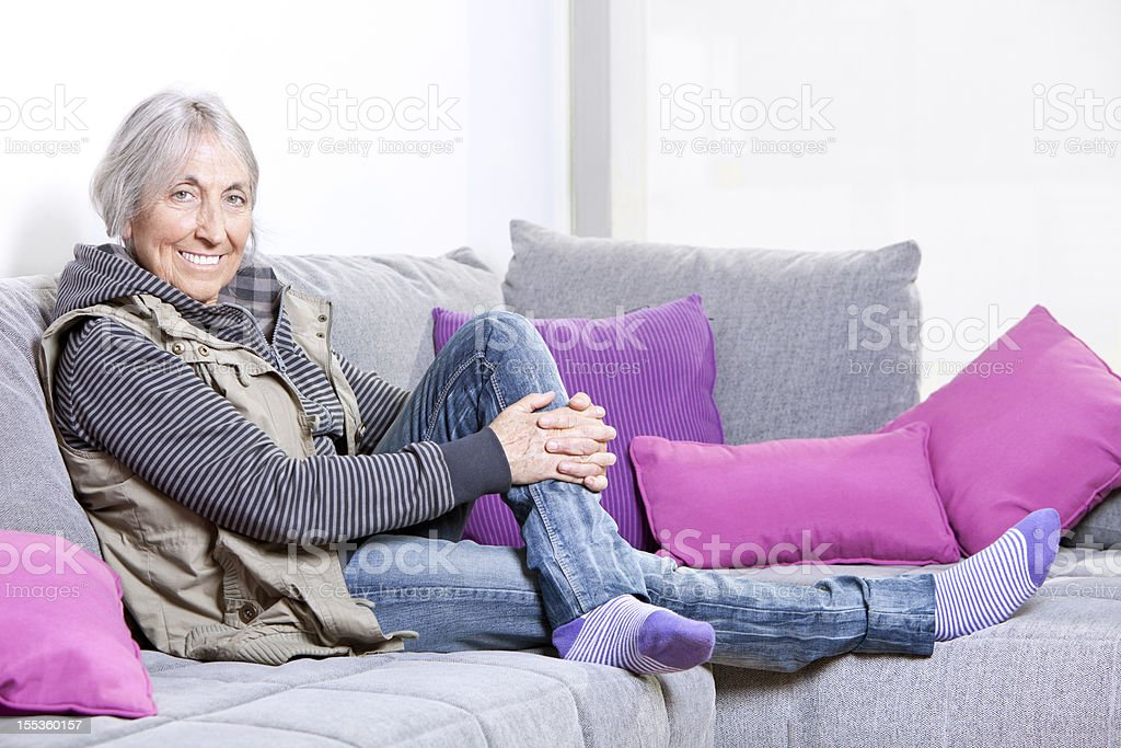 Relaxed elderly woman on sofa stock photo