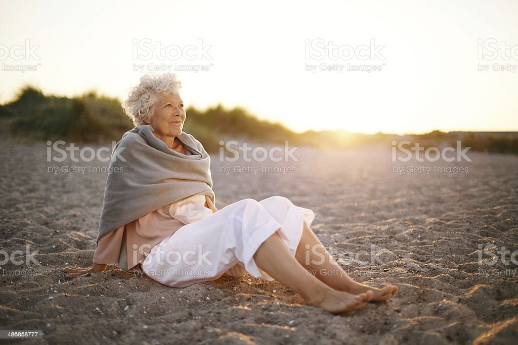 Relaxed elderly woman sitting on the beach stock photo