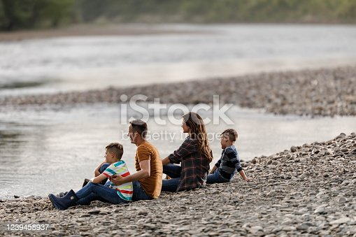 Young happy family relaxing on a stone beach by the river and looking at view. Copy space.