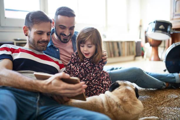リラックスした父親とデジタルタブレットを使用して3歳の娘 - lgbtqi  ストックフォトと画像