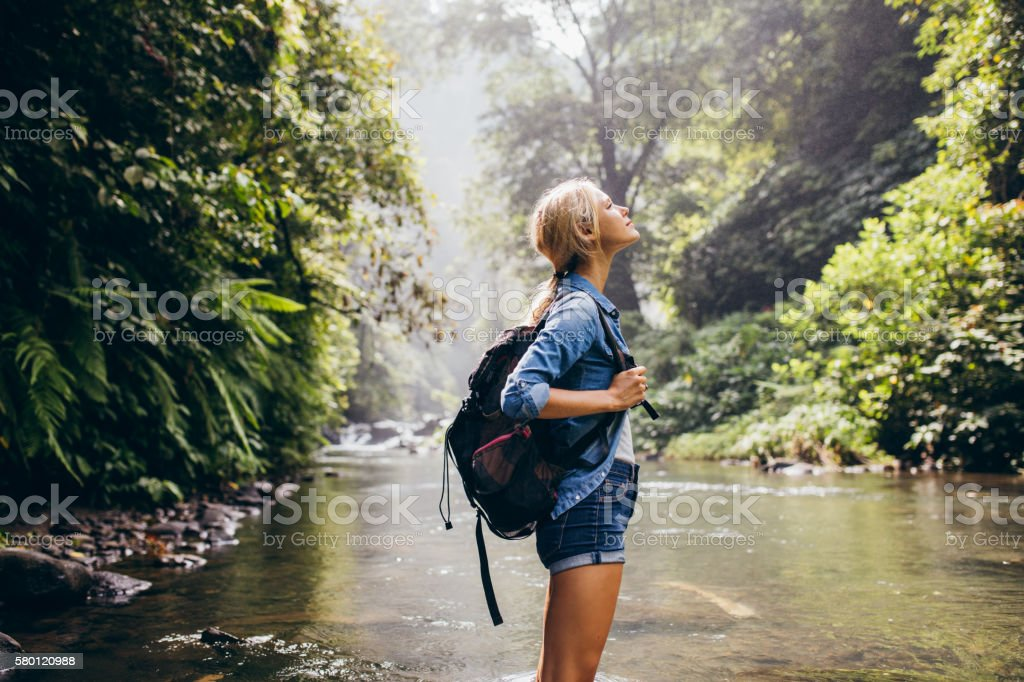 Relaxed female hiker standing by the stream ストックフォト