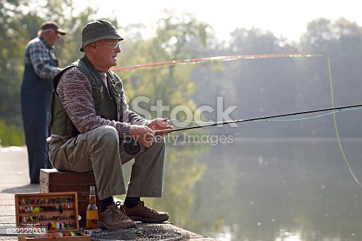 483319252 istock photo Relaxed fisherman fishing from the dock in river 522222033