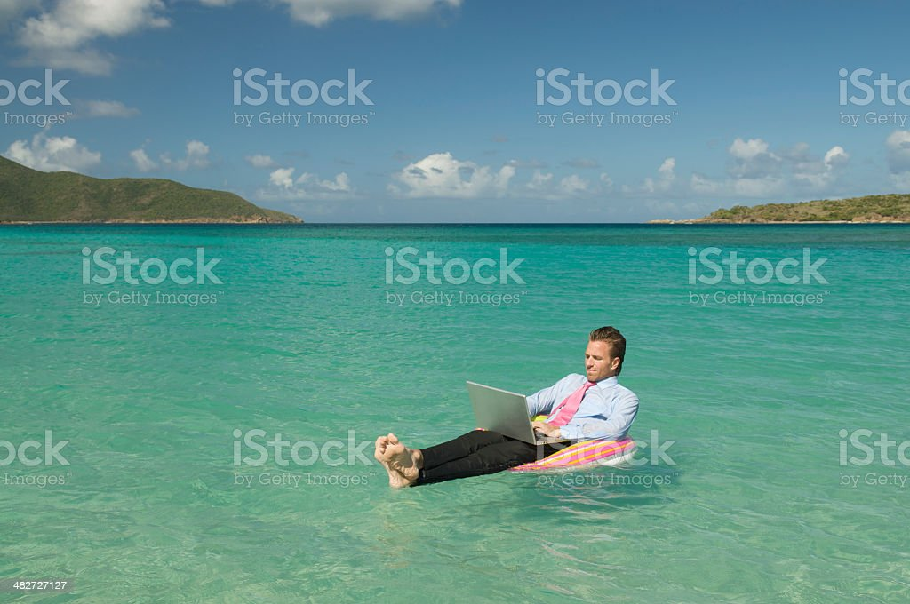 Relaxed Floating Businessman Working Adrift with Laptop royalty-free stock photo