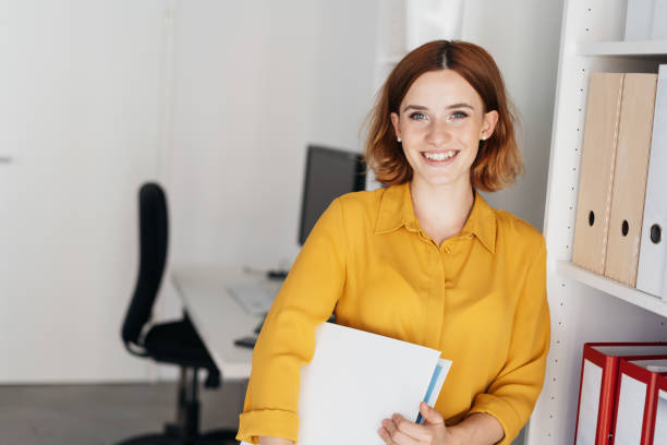 Relaxed friendly businesswoman holding a binder stock photo
