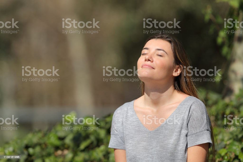 Relaxed girl breathing fresh air in a park a sunny day Relaxed girl breathing fresh air in a park a sunny day Active Lifestyle Stock Photo