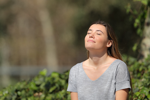 Relaxed Girl Breathing Fresh Air In A Park A Sunny Day Stock Photo - Download Image Now