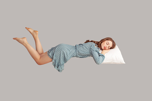 Relaxed girl in vintage ruffle dress levitating in mid-air, sleeping on stomach lying comfortable cozy on pillow, keeping eyes closed, watching peaceful dream. indoor studio shot isolated on gray