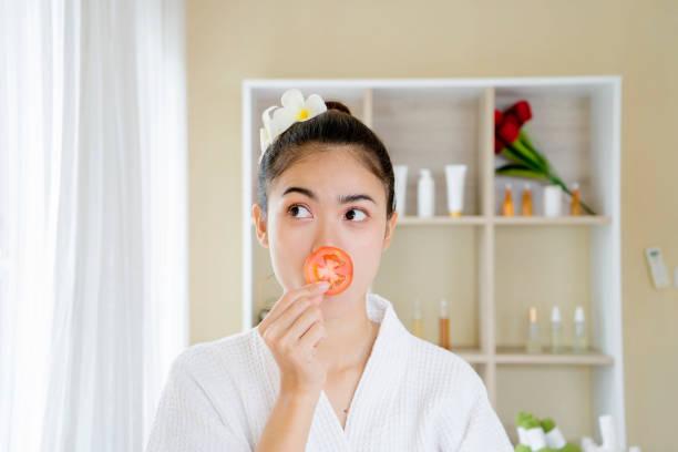 Chica relajada sonriendo escondiendo el ojo detrás de la rebanada de tomate. - foto de stock