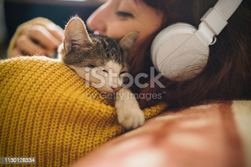 Woman at home listening to music with kitten napping on her shoulder