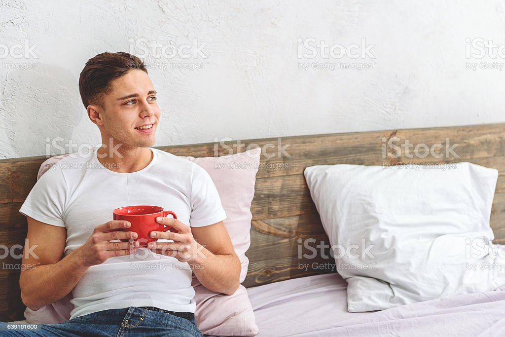 Relaxed Guy Drinking Hot Beverage In Bedroom Stock Photo More
