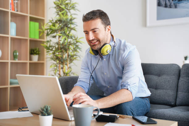 Relaxed guy having fun at home using internet streaming connection stock photo