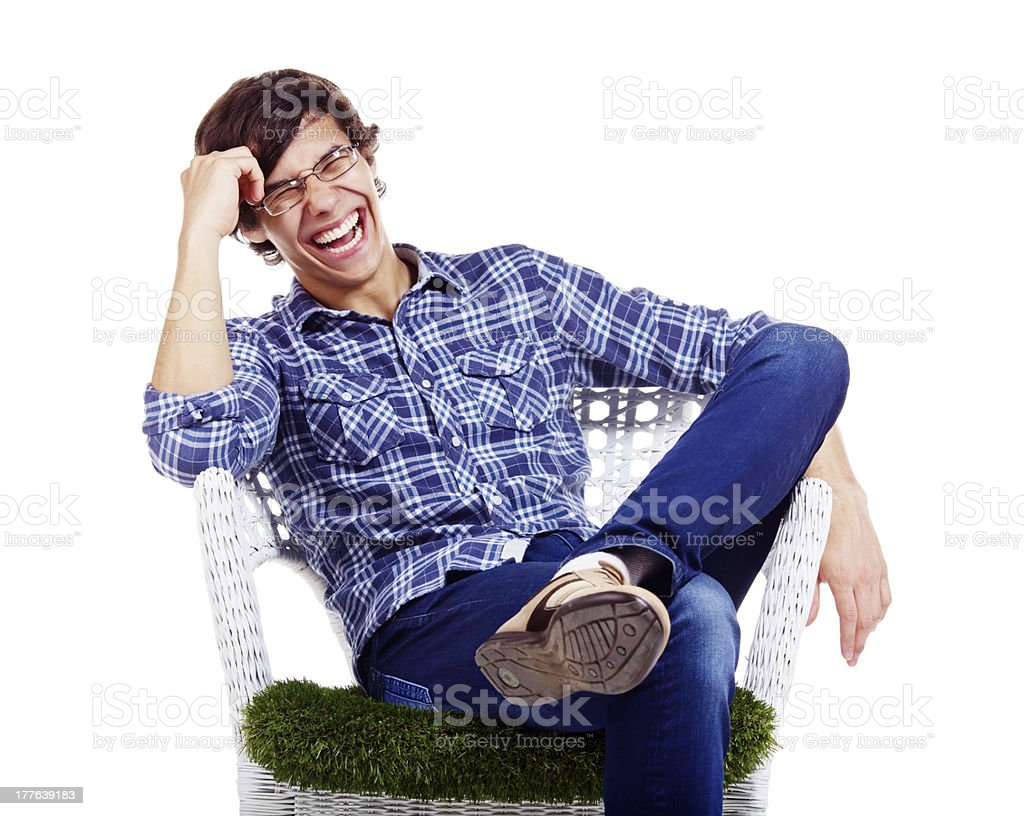 Relaxed guy laughing in armchair royalty-free stock photo