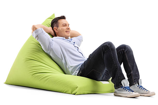 relaxed guy laying on a beanbag - stuhlpolster stock-fotos und bilder