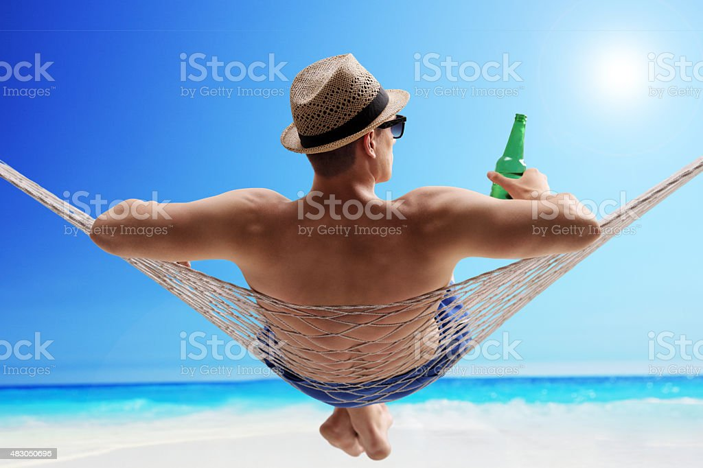 Relaxed guy lying in a hammock and drinking beer stock photo
