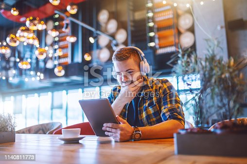 Relaxed handsome Caucasian man in plaid shirt and with headphones on ears using tablet. On desk coffee, coffee shop interior.