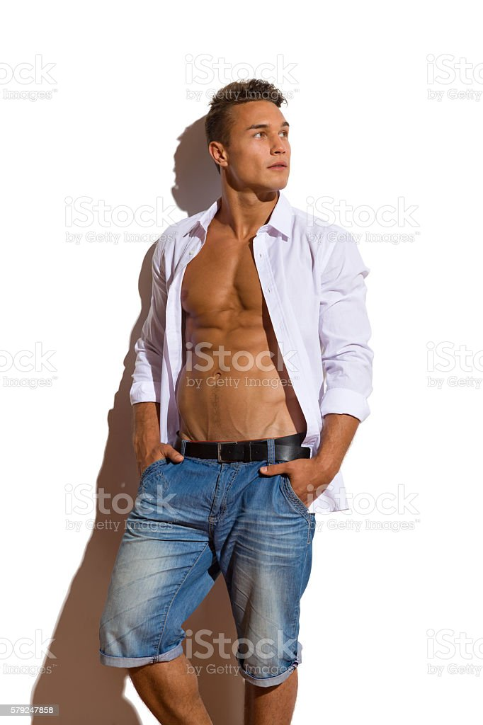 Relaxed Handsome Man In White Unbuttoned Shirt Looking Away stock photo