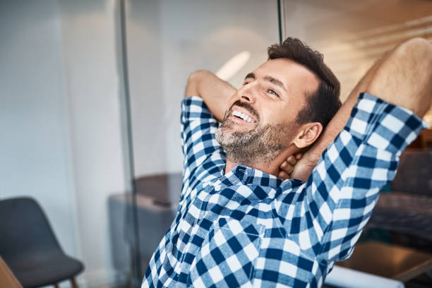 Relaxed handsome man sitting at desk smiling stock photo