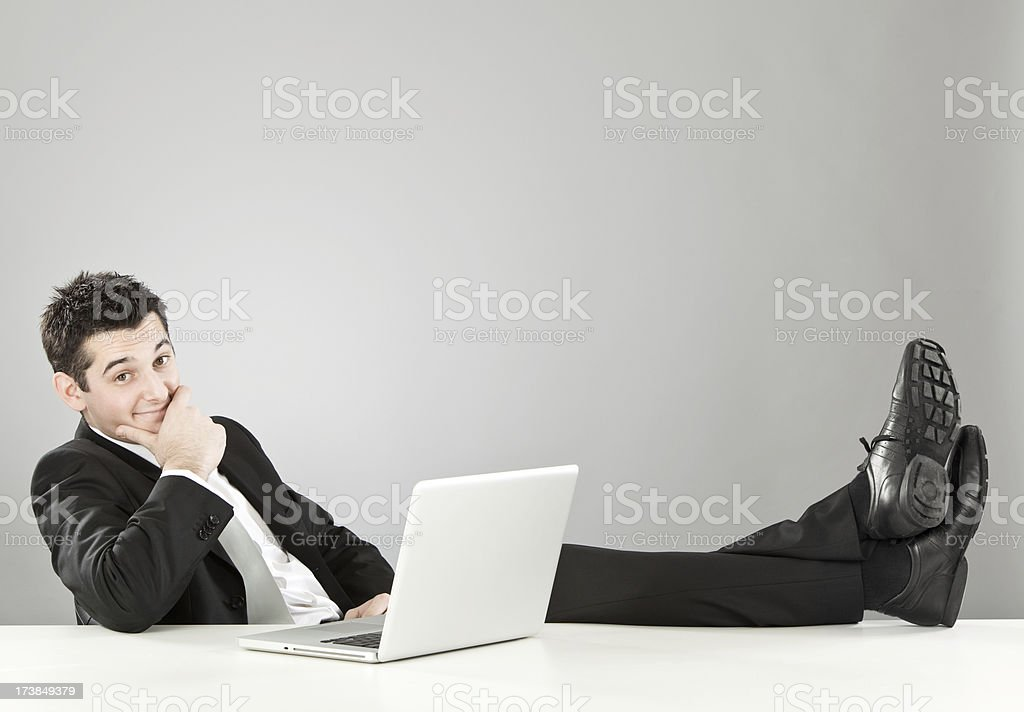 relaxed happy businessman with laptop at desk royalty-free stock photo
