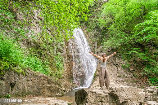 Relaxed happy female tourist standing in front of a waterfall with arms wide open Teteven, Bulgaria. The scene is situated in the woods of Stara, Planina (Old Mountain) in Teteven, Bulgaria (Eastern Europe). Picture was taken with DJI Phantom 4 Pro drone.