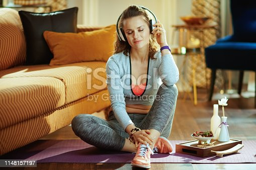 973962328istockphoto relaxed healthy sports woman listening to music with headphones 1148157197