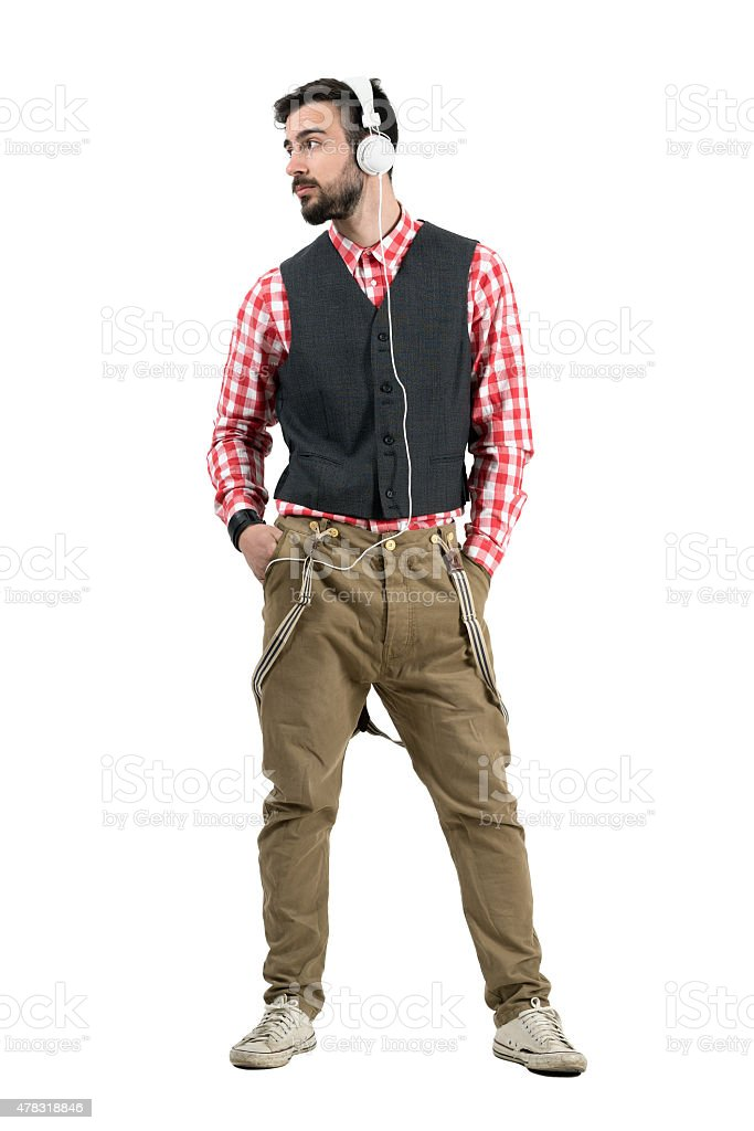 Relaxed hipster listening mp3 player looking away stock photo