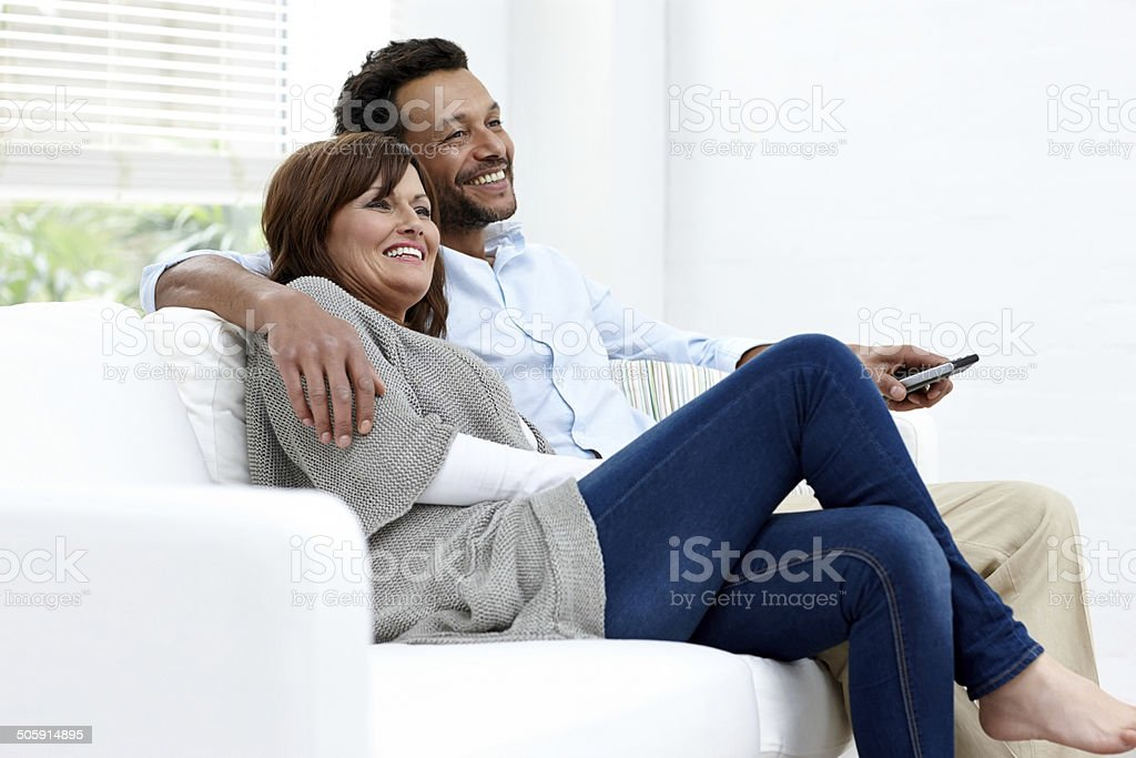 Relaxed interracial couple enjoying watching TV at home stock photo