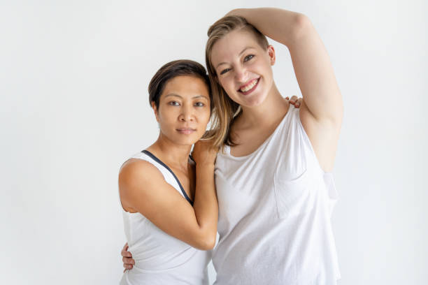 Relaxed lesbian couple embracing and looking at camera stock photo