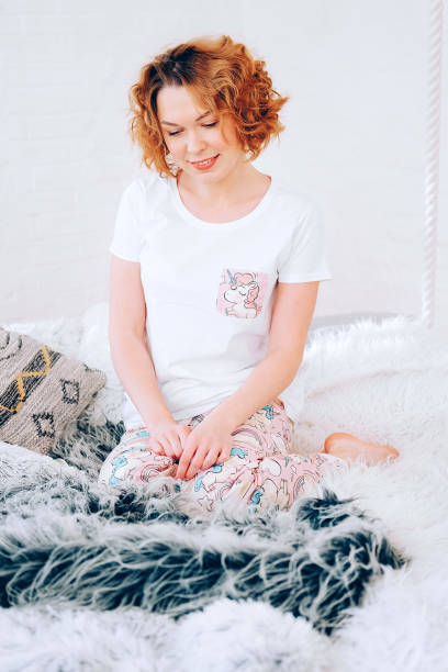 relaxed lifestyle. happy young redhead woman with short curly hair in her pyjamas spending time in bed. lazy morning concept. - unicorn bed imagens e fotografias de stock