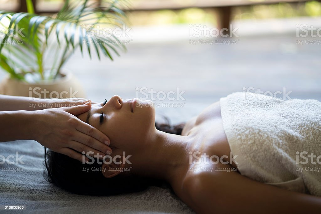 Relaxed Malaysian woman having a head massage at the spa. stock photo