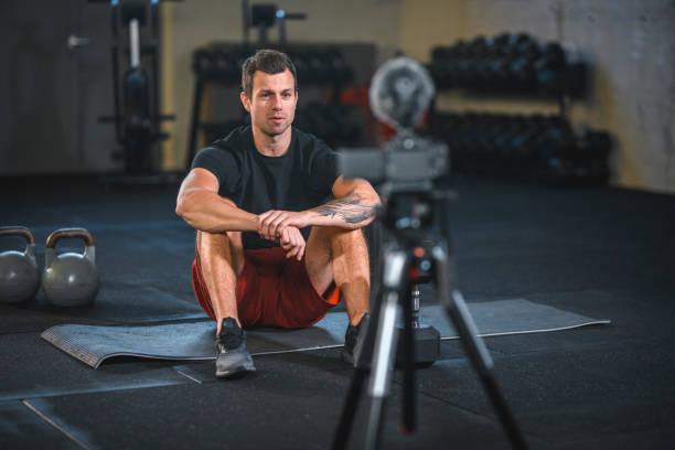relaxed male fitness trainer making fitness vlog at gym - dodatkowa praca zdjęcia i obrazy z banku zdjęć